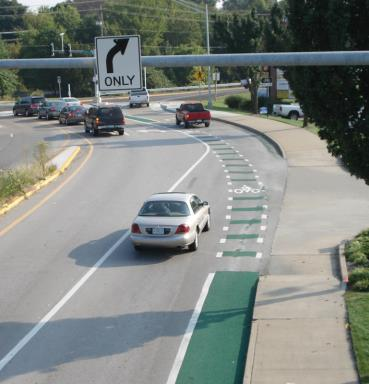 One of two green merge-and-weave intersection treatments.